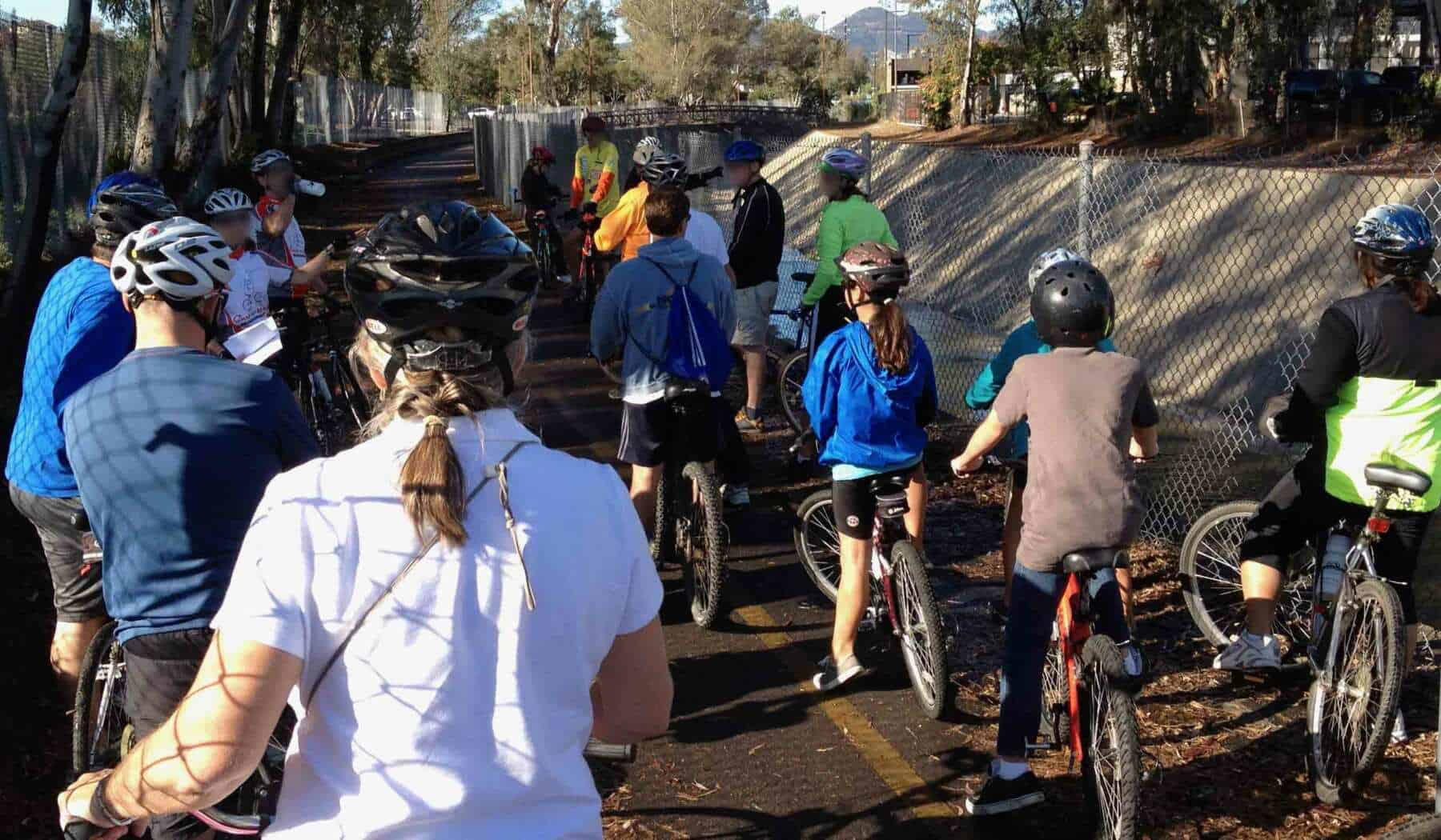 A mix of 16 adults & children stop during a bike ride to learn about a nearby creek.