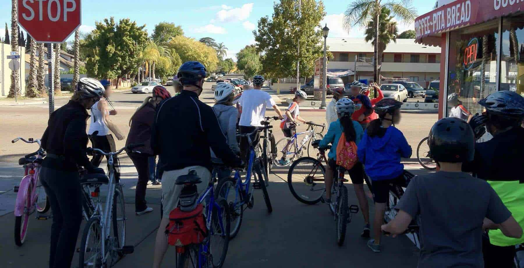 A mix of 15 adults & children stop during a bike ride to shop at a corner market.