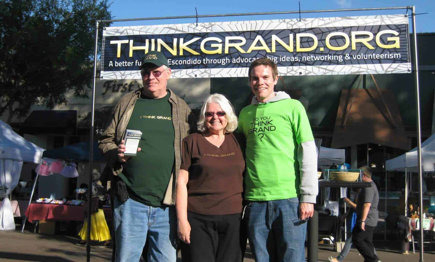 Dave Woods & his parents stand in front of a booth below a banner that reads thinkgrand.org.