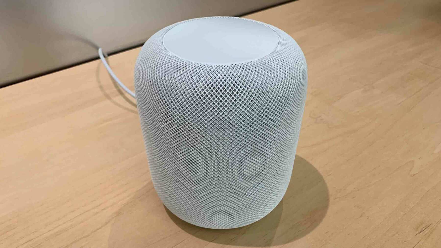 A white Apple HomePod sitting on a blonde woodgrain tabletop.